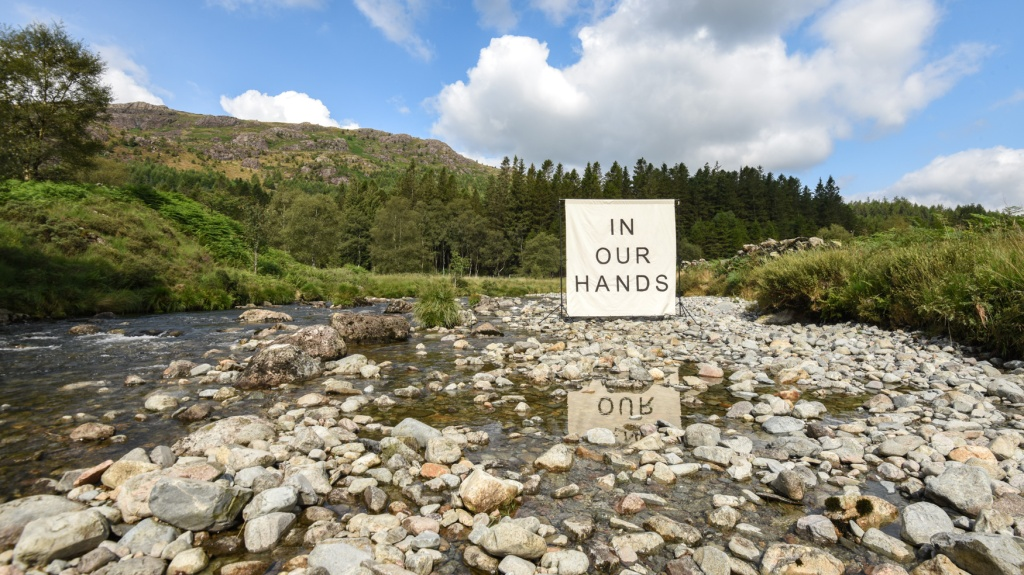 A large white canvas erected on a river bed in the Duddon Valley. The canvas has the words IN OUR HANDS written on it in black.