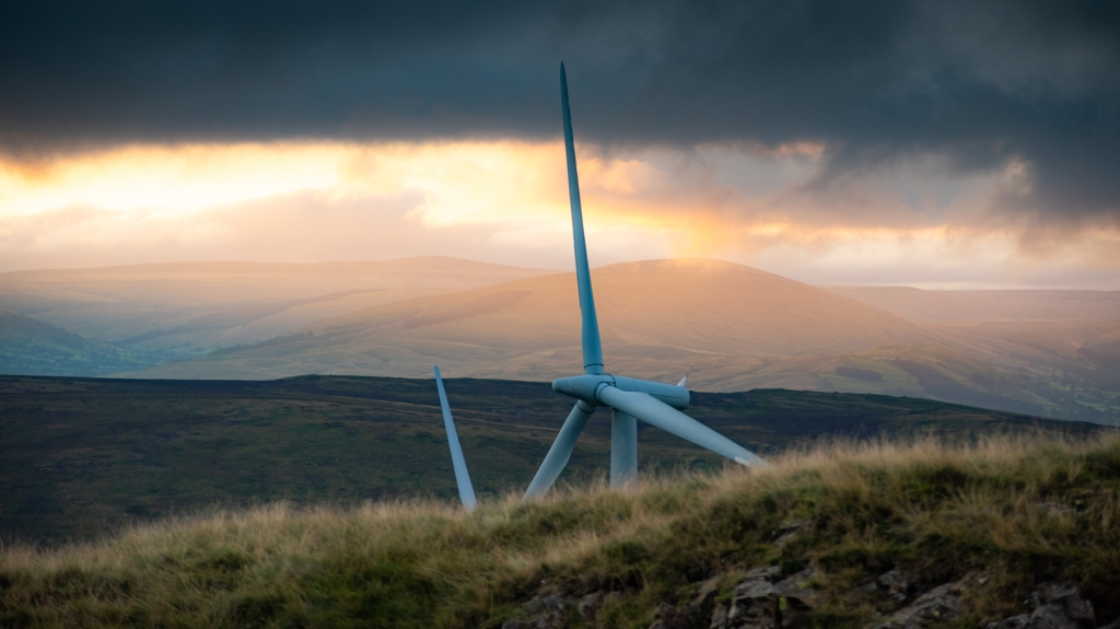 Wind turbines from a small fell in eastern Cumbria, with heavy clouds and hills in the background.
